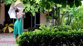Η νέα όμορφη γυναίκα στην πράσινη ομπρέλα εκμετάλλευσης φορεμάτων περπατά στη βροχερή ημέρα Το κορίτσι απολαμβάνει της βροχής 384 φιλμ μικρού μήκους