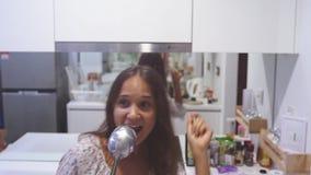 Η νέα όμορφη γυναίκα στους χορούς πυτζαμών cookes και τραγουδά το τραγούδι με την κουτάλα μαγειρεύοντας στη σύγχρονη κουζίνα στο  απόθεμα βίντεο
