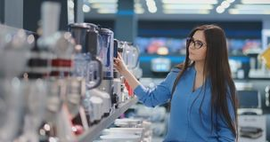 Η νέα όμορφη γυναίκα στο κατάστημα συσκευών επιλέγει για την κουζίνα της ένα μπλέντερ που κοιτάζει και που κρατά στα χέρια της φιλμ μικρού μήκους