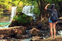 Η νέα όμορφη γυναίκα στο μπικίνι εξερευνά τον καταρράκτη που κρύβεται στην τροπική ζούγκλα στο υπόβαθρο που καταπλήσσει την άγρια Στοκ Εικόνα