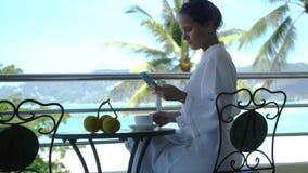 Η νέα όμορφη γυναίκα στο μπουρνούζι κάθεται σε έναν καφέ κατανάλωσης μπαλκονιών και χρησιμοποιεί το κινητό τηλέφωνο στην καταπληκ απόθεμα βίντεο