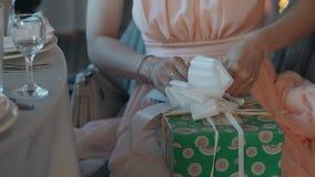 Η νέα όμορφη γυναίκα συσκευάζει το δώρο στο μέσο κιβώτιο σχεδίων μεγέθους πράσινο με τις άσπρες ταινίες και το μεγάλο ελκυστικό τ απόθεμα βίντεο