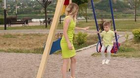 Η νέα όμορφη γυναίκα την κυλά λίγος γιος σε μια ταλάντευση στο πάρκο το καλοκαίρι φιλμ μικρού μήκους