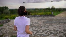 Η νέα όμορφη γυναίκα τρέχει στο πάρκο Λήφθείτε από την πλάτη Σε αργή κίνηση απόθεμα βίντεο
