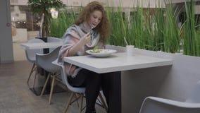 Η νέα όμορφη γυναίκα τρώει τη caesar σαλάτα σε έναν καφέ απόθεμα βίντεο