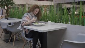 Η νέα όμορφη γυναίκα τρώει τη caesar σαλάτα σε έναν καφέ φιλμ μικρού μήκους