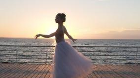 Η νέα όμορφη γυναίκα χορεύει φορώντας το άσπρο tutu στην ανατολή ή το ηλιοβασίλεμα Εκτέλεση του κλασικού χορευτικού βήματος μπαλέ απόθεμα βίντεο