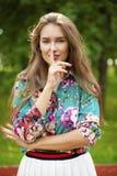 Η νέα όμορφη γυναίκα brunette έχει βάλει το δείκτη στα χείλια ως SIG Στοκ φωτογραφία με δικαίωμα ελεύθερης χρήσης