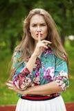 Η νέα όμορφη γυναίκα brunette έχει βάλει το δείκτη στα χείλια ως SIG Στοκ Εικόνες