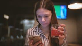 Η νέα όμορφη γυναίκα brunette διαβάζει κάτι στο κινητό τηλέφωνο και πίνει το κόκκινο βοτανικό τσάι στον καφέ απόθεμα βίντεο
