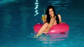 Η νέα όμορφη γυναίκα brunette πίνει το φρέσκο κοκτέιλ στη λίμνη φιλμ μικρού μήκους