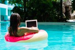 Η νέα όμορφη γυναίκα freelancer επιπλέει στη θάλασσα ή στη λίμνη σε έναν κολυμπώντας κύκλο Ένα κορίτσι χαλαρώνει στοκ φωτογραφία με δικαίωμα ελεύθερης χρήσης