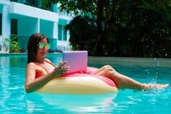 Η νέα όμορφη γυναίκα freelancer επιπλέει στη θάλασσα ή στη λίμνη σε έναν κολυμπώντας κύκλο Ένα κορίτσι χαλαρώνει στοκ εικόνες