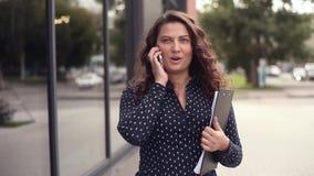 Η νέα όμορφη επιχειρησιακή γυναίκα περπατά δίπλα σε ένα κτίριο γραφείων με τα έγγραφα και μιλά στο τηλέφωνο ενώ αποσπάται απόθεμα βίντεο