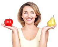 Η νέα όμορφη ευτυχής γυναίκα κρατά το μήλο και το αχλάδι. Στοκ εικόνα με δικαίωμα ελεύθερης χρήσης