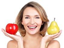Η νέα όμορφη ευτυχής γυναίκα κρατά το μήλο και το αχλάδι Στοκ εικόνες με δικαίωμα ελεύθερης χρήσης