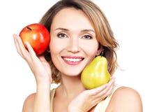 Η νέα όμορφη ευτυχής γυναίκα κρατά το μήλο και το αχλάδι Στοκ Εικόνα