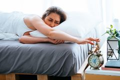 Η νέα όμορφη και ελκυστική καυκάσια γυναίκα ξύπνησε επάνω να βρεθεί στο κρεβάτι στο πρωί με την κούραση και την τεμπελιά στην άσπ στοκ φωτογραφία