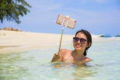 Η νέα όμορφη και ευτυχής ασιατική κινεζική γυναίκα που έχει τη διασκέδαση στο θαλάσσιο νερό που παίρνει selfie απεικονίζει με την Στοκ φωτογραφία με δικαίωμα ελεύθερης χρήσης