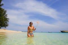 Η νέα όμορφη και ευτυχής ασιατική κινεζική γυναίκα που έχει τη διασκέδαση στο θαλάσσιο νερό που παίρνει selfie απεικονίζει με την Στοκ Φωτογραφίες