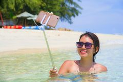Η νέα όμορφη και ευτυχής ασιατική κινεζική γυναίκα που έχει τη διασκέδαση στο θαλάσσιο νερό που παίρνει selfie απεικονίζει με την Στοκ Φωτογραφία