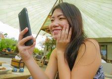 Η νέα όμορφη και ευτυχής ασιατική κινεζική γυναίκα που χρησιμοποιεί τα κοινωνικά μέσα app Διαδικτύου στο κινητό τηλέφωνο που χαμο Στοκ Εικόνες