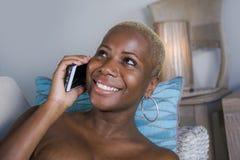 Η νέα όμορφη και ευτυχής μαύρη αμερικανική γυναίκα afro ξαπλώνει στο σπίτι το χαλαρωμένο χαμόγελο εύθυμο με το κινητό τηλέφωνο πο στοκ φωτογραφία με δικαίωμα ελεύθερης χρήσης