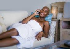 Η νέα όμορφη και ευτυχής μαύρη αμερικανική γυναίκα afro ξαπλώνει στο σπίτι το χαλαρωμένο χαμόγελο εύθυμο με το κινητό τηλέφωνο πο στοκ φωτογραφίες