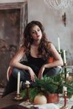 Η νέα όμορφη κυρία στο φόρεμα βραδιού στο εσωτερικό σοφιτών κάθεται στον πίνακα με τα κεριά και τους κλαδίσκους έλατου Στοκ Φωτογραφία