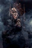 Η νέα όμορφη μάγισσα κάθεται σε μια καρέκλα Φωτεινός αποτελέστε, κρανίο, θέμα αποκριών καπνού στοκ εικόνες με δικαίωμα ελεύθερης χρήσης