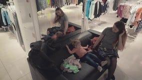Η νέα όμορφη μητέρα με ένα μικρό παιδί κορών σε ένα κατάστημα ιματισμού κοιτάζει στον καθρέφτη, mom διορθώνει τις πλεξίδες φιλμ μικρού μήκους