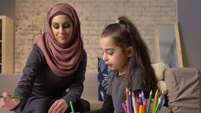 Η νέα όμορφη μητέρα στο hijab που κάνει τα μαθήματα εργασίας, λίγη κόρη επιλέγει τα μολύβια χρώματος, σύρει, παιδιά ` s φιλμ μικρού μήκους
