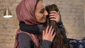 Η νέα όμορφη μητέρα στο hijab την αγκαλιάζει λίγη κόρη, που κάθεται στον καναπέ, οικογένεια, χαμόγελο, έννοια 50 εγχώριου cosines απόθεμα βίντεο