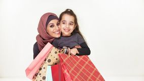 Η νέα όμορφη μητέρα στο hijab την αγκαλιάζει λίγη κόρη, που κρατά τις τσάντες αγορών, χαμόγελο, ευτυχής οικογένεια στο λευκό απόθεμα βίντεο
