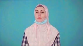 Η νέα όμορφη μουσουλμανική γυναίκα στην ιατρική μάσκα, βγάζει τη μάσκα που χαμογελά και που εξετάζει τη κάμερα απόθεμα βίντεο