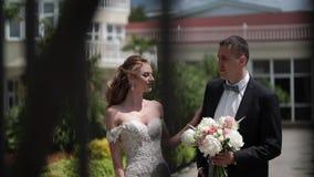 Η νέα όμορφη νύφη σε ένα γαμήλιο φόρεμα πηγαίνει στο νεόνυμφο Συνεδρίαση των newlyweds φιλμ μικρού μήκους