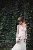 Η νέα όμορφη νύφη σε ένα κομψό φόρεμα στέκεται στον τομέα κοντά στο δάσος και κρατά την ανθοδέσμη στοκ φωτογραφία