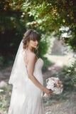 Η νέα όμορφη νύφη σε ένα κομψό φόρεμα στέκεται στον τομέα κοντά στο δάσος και κρατά την ανθοδέσμη στοκ εικόνες