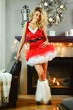 Η νέα όμορφη ξανθή γυναίκα έντυσε ως προκλητικός αρωγός Santas στο κόκκινο φόρεμα και η τοποθέτηση καταστημάτων πλεκτών ειδών διχ στοκ εικόνες με δικαίωμα ελεύθερης χρήσης