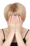 Η νέα όμορφη ξανθή γυναίκα καλύπτει το πρόσωπό της στοκ φωτογραφία με δικαίωμα ελεύθερης χρήσης