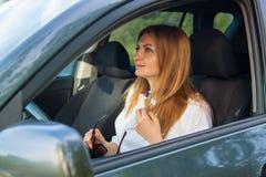 Η νέα όμορφη ξανθή γυναίκα οδηγεί ένα αυτοκίνητο στοκ εικόνα