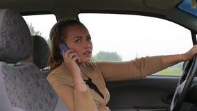 Η νέα όμορφη ομιλία κοριτσιών χρησιμοποιεί το smartphone σας καθμένος πίσω από τη ρόδα ενός αυτοκινήτου απόθεμα βίντεο