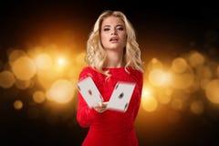 Η νέα όμορφη συναισθηματική γυναίκα ρίχνει τις κάρτες σε ένα μαύρο υπόβαθρο στο στούντιο πόκερ στοκ εικόνα
