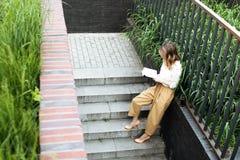 Η νέα όμορφη συνεδρίαση γυναικών στο ανοιγμένο τσάι κατανάλωσης παραθύρων και ανάγνωση ενός βιβλίου απολαμβάνει του υπολοίπου στοκ εικόνα