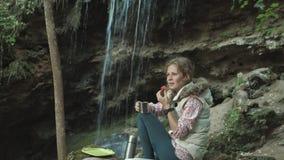 Η νέα όμορφη συνεδρίαση τουριστών γυναικών στη στάση στο δασικό όμορφο κορίτσι τουριστών brunette κάθεται στο δάσος κοντά στο κόκ απόθεμα βίντεο