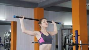 Η νέα όμορφη φίλαθλη ανύψωση κοριτσιών barbell φράζει στη γυμναστική, άσκηση ώμων, μπροστινή πλάγια όψη 60 fps απόθεμα βίντεο