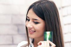 Η νέα όμορφη χαμογελώντας γυναίκα αγοράζει on-line στοκ φωτογραφία με δικαίωμα ελεύθερης χρήσης