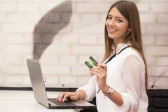 Η νέα όμορφη χαμογελώντας γυναίκα κάθεται σε έναν πίνακα και αγοράζει on-line στοκ εικόνα
