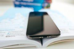 Η νέα Apple Iphone Χ smartphone ναυαρχίδων που τοποθετείται στο βιβλίο ταξιδιού Στοκ Εικόνες