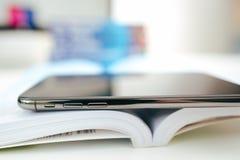 Η νέα Apple Iphone Χ smartphone ναυαρχίδων που τοποθετείται στο βιβλίο ταξιδιού Στοκ Φωτογραφίες